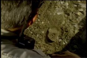 Police officer examining a boot print in the dirt