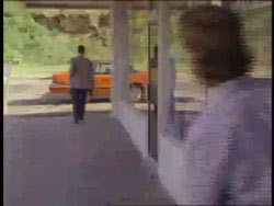 Woman watching a man walk towards his orange convertable