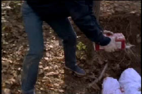 Bishop pouring gasoline onto covered bodies in a shallow grave in the woods