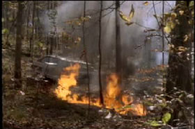 Fire burning behind a station wagon in the woods